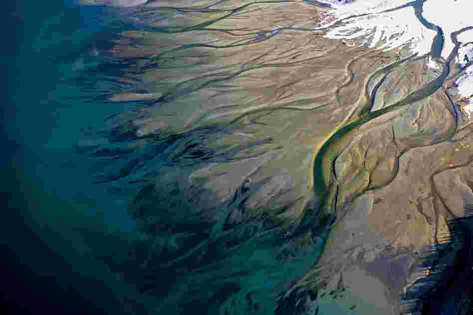 Tributaries of Lynn Canal, a spectacularly deep fjord in Alaska, wind across a muddy plain to empty into a blue-green bay.