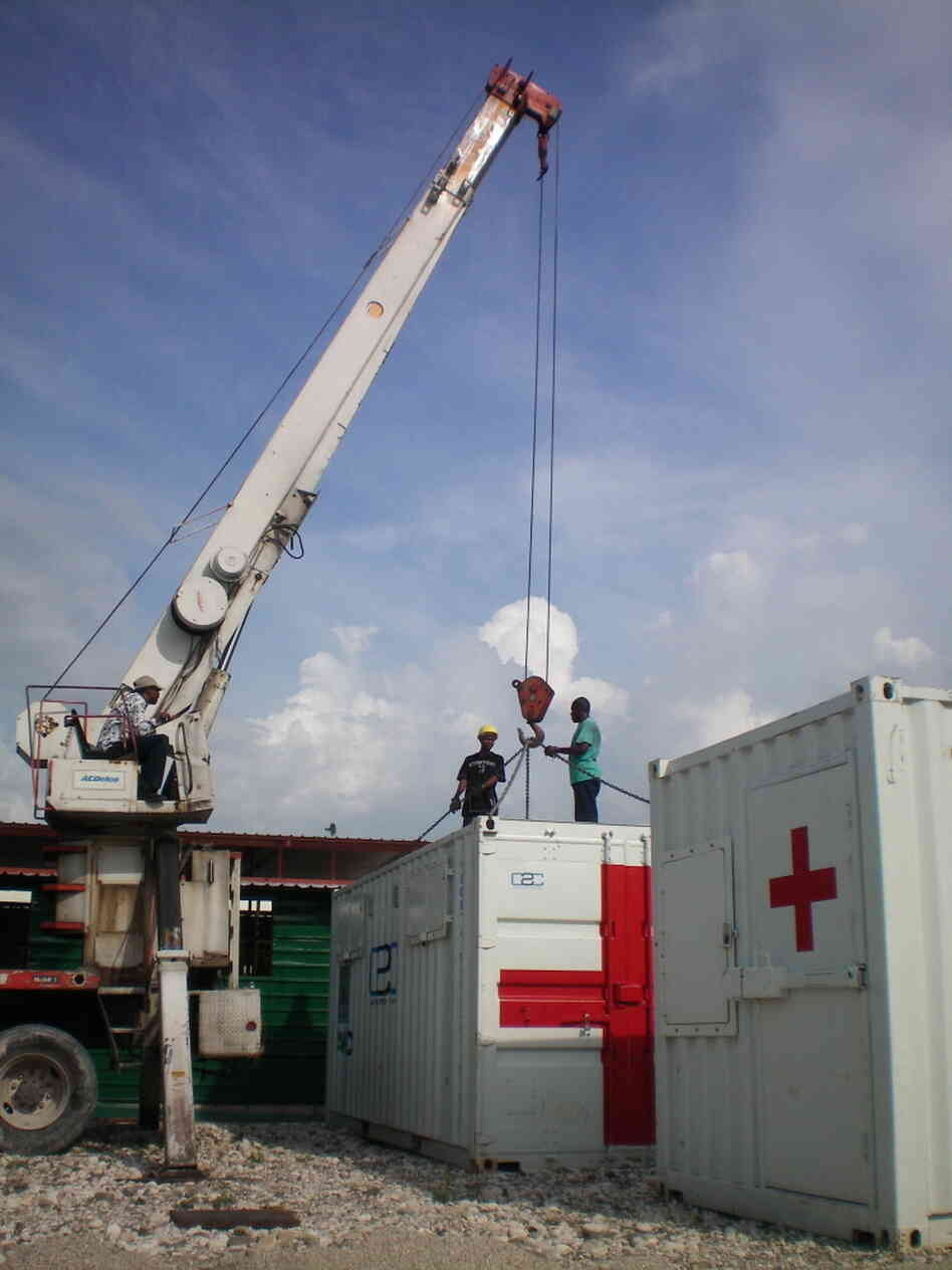 A crane deploys a health clinic constructed from a shipping container