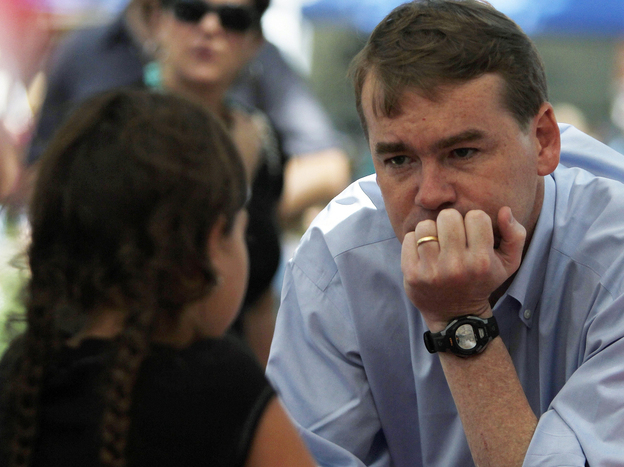 Sen. Michael Bennet (D-CO) visits with a young girl as he campaigns in downtown Colorado Springs on Aug. 9. After surviving a tough primary challenge, Bennet is now in a close race with Tea Party-backed Republican Ken Buck.
