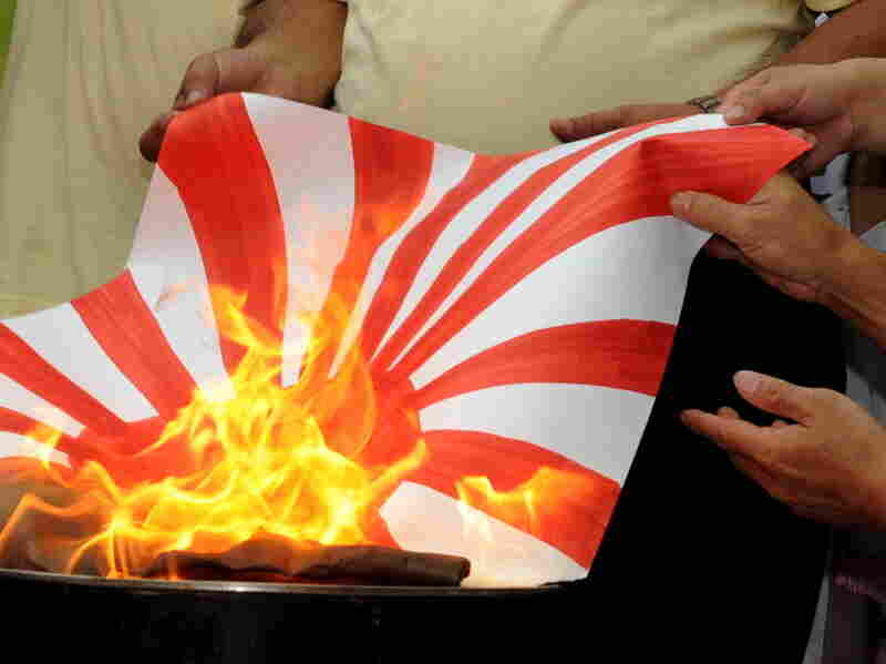 Chinese protesters burn a Japanese flag at a Sept. 18 demonstration in Hong Kong.