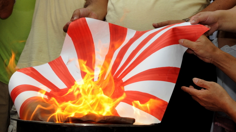 Chinese protesters burn a Japanese flag during a demonstration in front of the Japanese consulate in Hong Kong on Sept. 18.