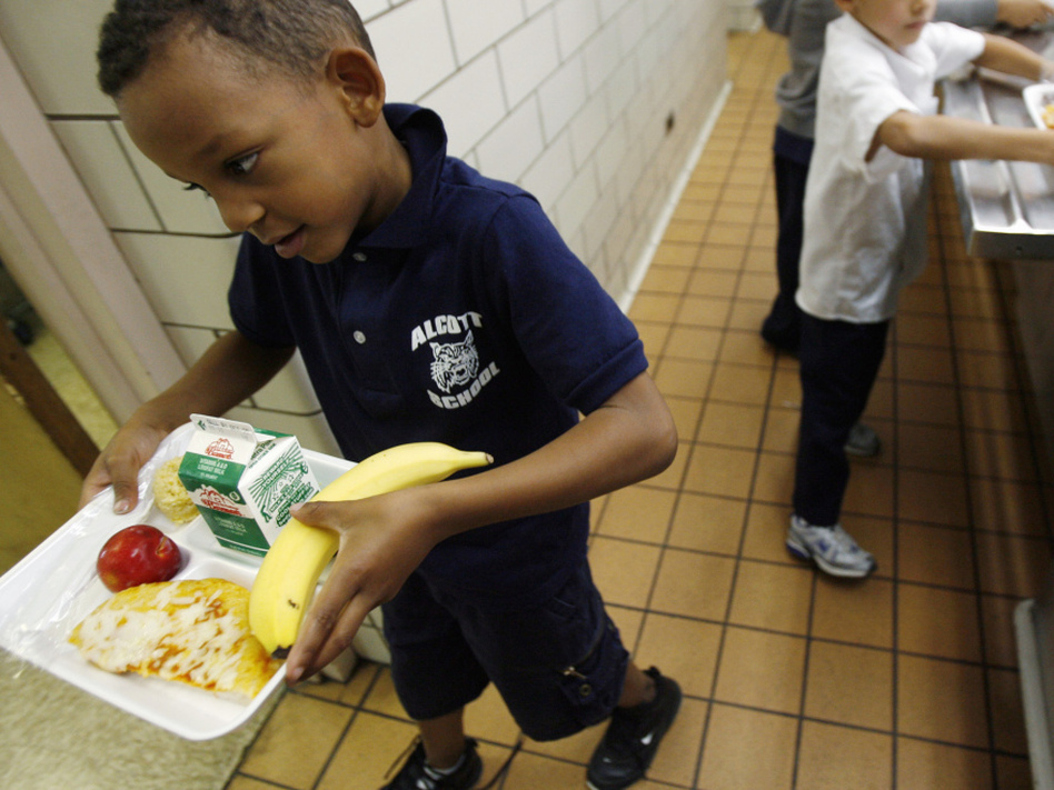 A student at the Louisa May Alcott Elementary School in Chicago carries his lunch tray.