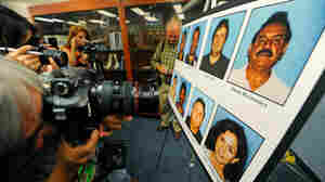 Photographers photograph a display of current and former Bell council members who were arrested.