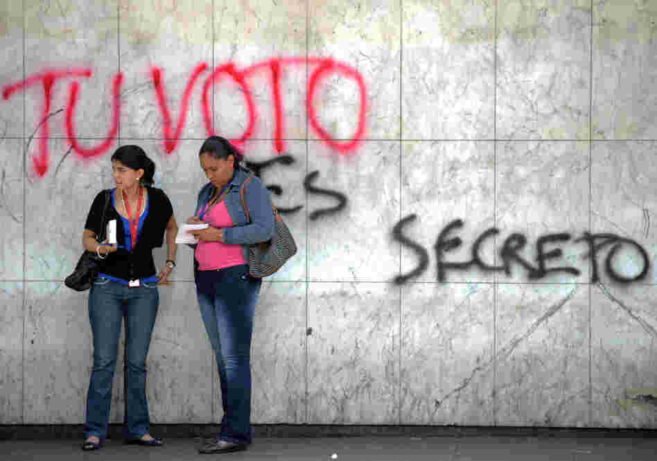 Two women talk in front of a graffiti al
