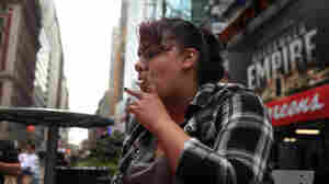 Helene Martich smokes in a Times Square pedestrian island in New York City.