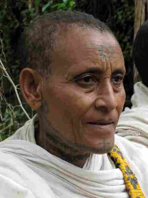 Orthodox Ethiopian women in the highlands often tattoo religious symbols to their faces and upper bodies. This woman distributes bread at a monastery.