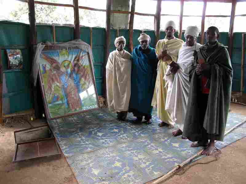 The trap door in the floor to the left of these religious men offers a view of slow-moving spring water said to be the source of the Blue Nile. The water at Gish Abay is believed to be holy. The faithful drink some everyday for good health.