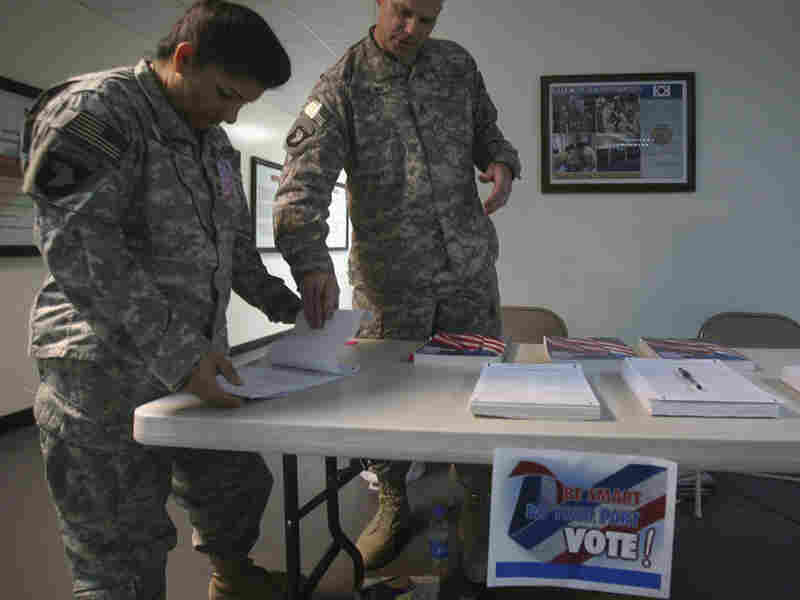 A U.S. member of Combined Joint Task Force 101, left, checks a voting ballot