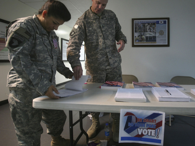 A U.S. member of Combined Joint Task Force 101 (left) checks a voting ballot before filling it out at a U.S. military base in Afghanistan. A new law  requires states to send absentee ballots overseas at least 45 days in  advance, and some states are now accepting votes via e-mail and fax.