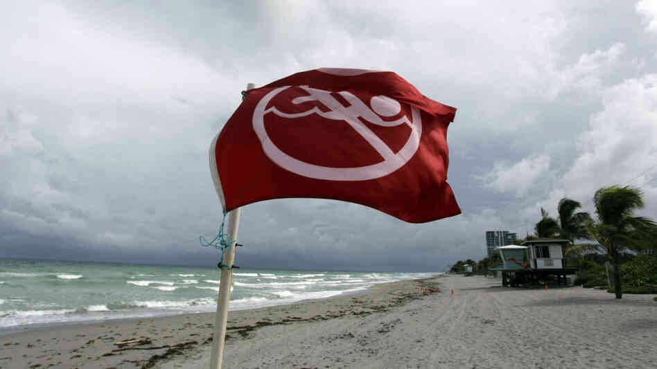 A warning flag on the empty beach in Dania Beach, Fla. Tuesday, Sept. 28, 2010.