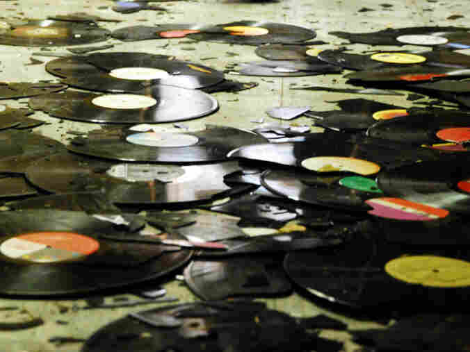 Broken records on the floor of a warehouse