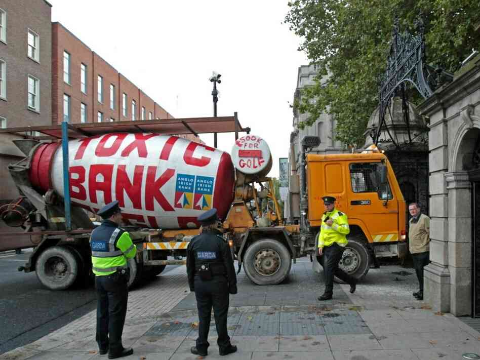 Irish police officers look at a cement mixer driven into the gate of Ireland's Parliament building.