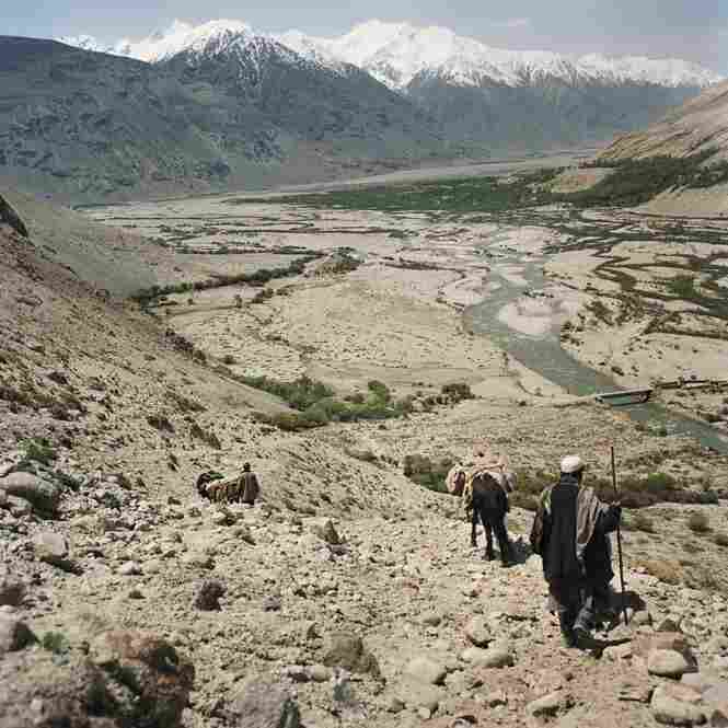 Wakhi men hike to the base of Big Pamir Mountain as they return to their village in the Wakhan Corridor, in the province of Badakshan in Afghanistan's northeast corner.