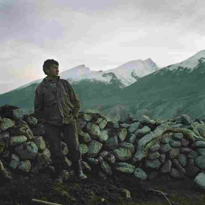 A young Wahki shepherd stands next to a sheep and goat pen after herding the flock in for the night.