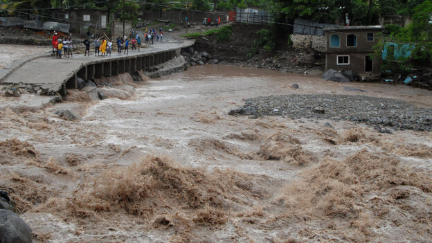 Jamaican residents watch flooding as they stand near a destroyed bridge that linked the towns of Kin