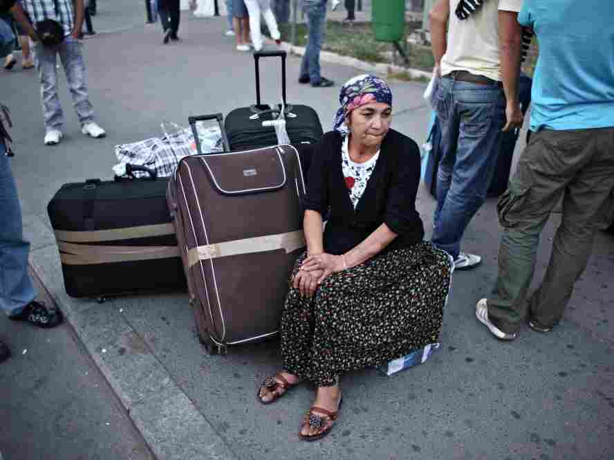 A Roma woman who was deported from France sits on her luggage in the airport in Bucharest.