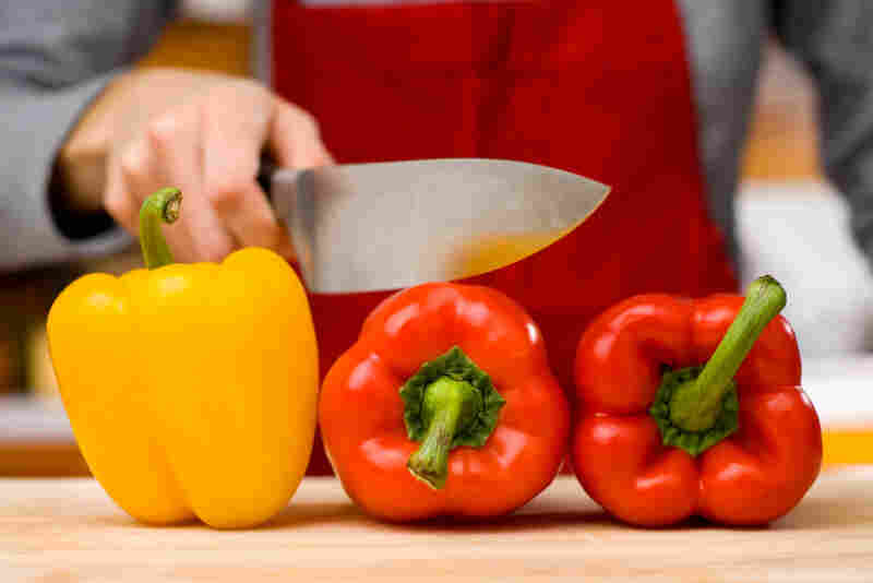 A woman holds a knife over a red pepper.