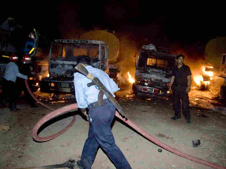 A Pakistani police officer helps fire fighters to extinguish burning oil tankers early Monday, Oct.