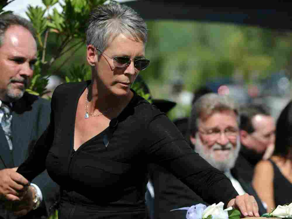 Actress Jamie Lee Curtis places a flower