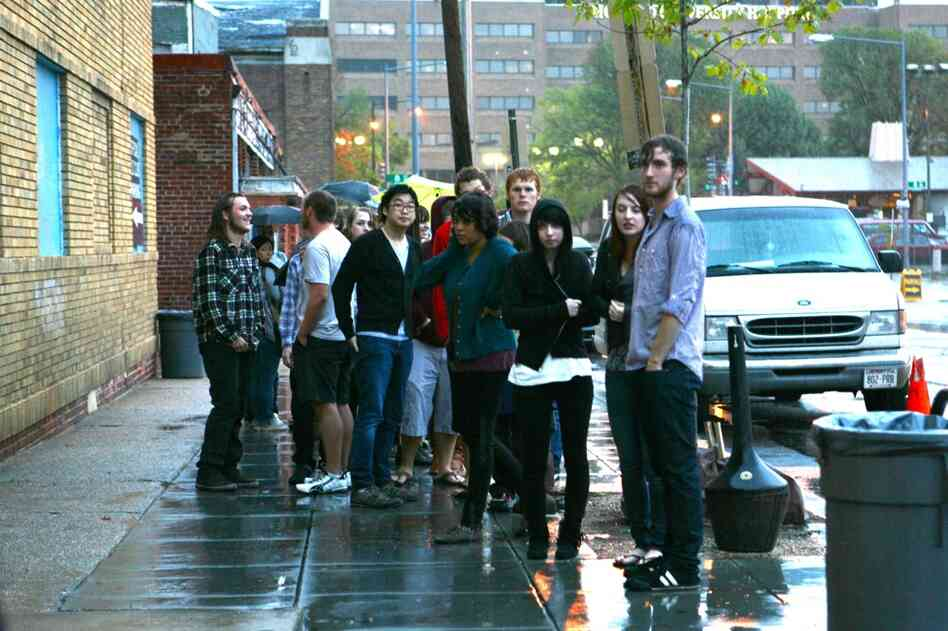 Fans wait outside in the rain to get into the 9:30 Club in Washington, D.C.