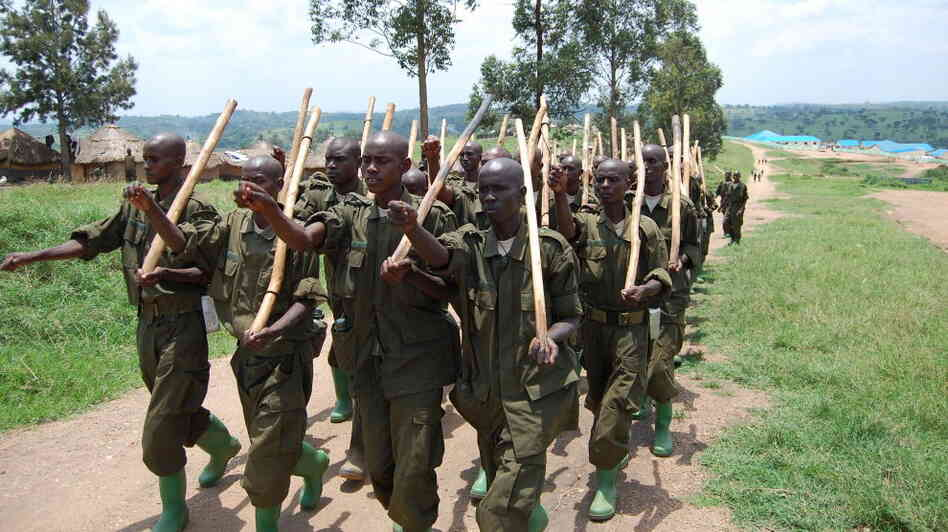 Somali soldiers march with sticks.