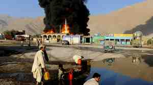 Local residents collect oil from the burning oil depot after gunmen attacked NATO tankers in Quetta
