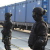 Guards stand in front of containers of highly enriched uranium in the port at Gdynia