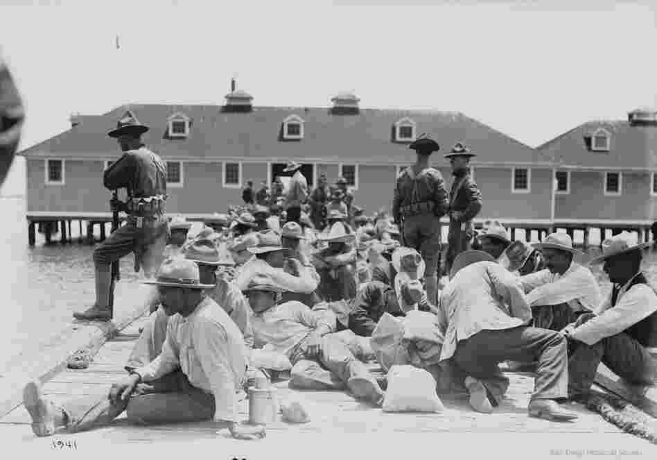 Mexican refugees on a dock under guard of U.S. soldiers, 1913.  At least 400 Mexicans entered the United States via Angel Island during the Mexican Revolution.