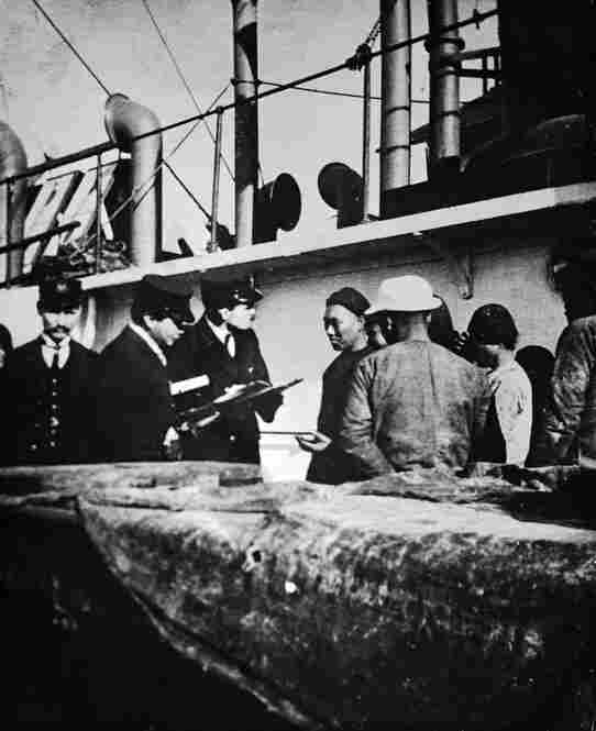 Immigration inspectors and an interpreter question Chinese immigrants arriving by ship in Portland, Ore., circa 1904-1910. Because the Chinese Exclusion Act of 1882 prohibited Chinese laborers from entering the United States, Chinese migrants were detained until their immigration status could be verified.