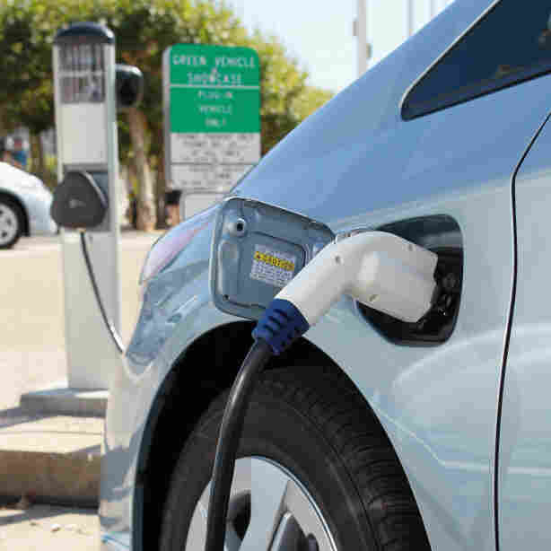 A power cable from a vehicle charging station is seen plugged into a Toyota Prius plug-in hybrid