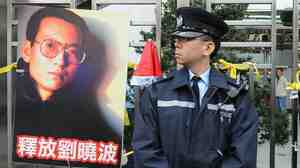 From December 25, 2009: A Hong Kong policeman stands next to a post of jailed Chinese dissident (now