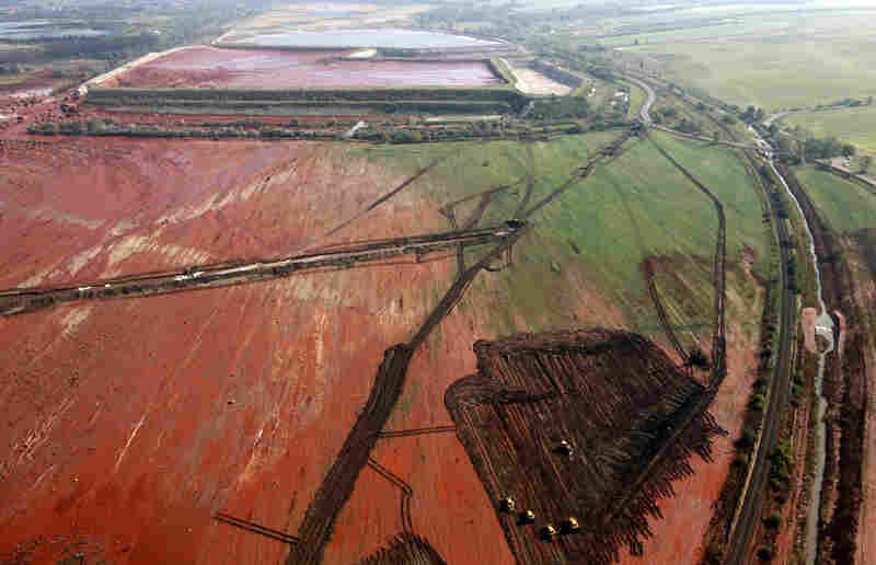 An aerial photo taken on Oct. 8, 2010, shows the ruptured wall of a red sludge reservoir of the Ajkai Timfoldgyar plant in Kolontar, Hungary. A wave of toxic red mud swept through the small village, killing five and injuring scores more.