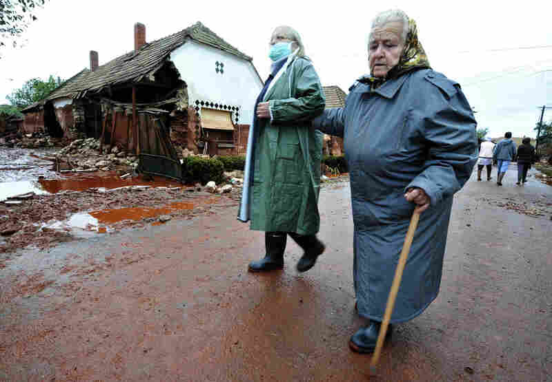 Residents return to check their homes in Kolontar on Oct. 6 , two days after a wave of toxic red mud swept through the small village.