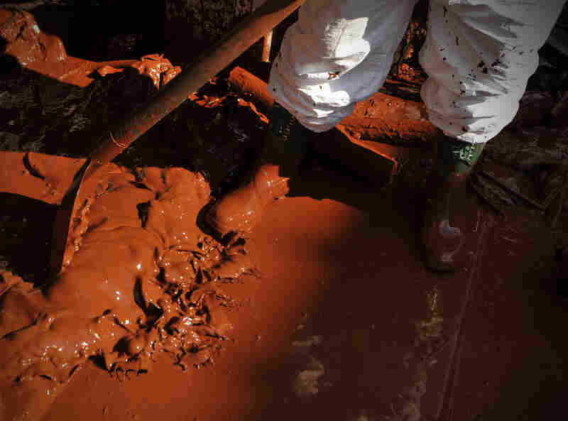 A Hungarian soldier, wearing protective gear, shovels toxic mud out of a house in Devecser, Oct. 7. The toxic red sludge that inundated three Hungarian villages reached Europe's Danube River on Thursday, but no immediate damage was evident, Hungary's rescue operations agency said.