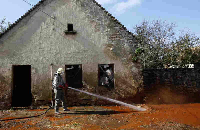 A Hungarian firefighter cleans a street flooded by toxic mud in Devecser, Hungary, Oct. 7. The flood of toxic mud killed several people and injured more than 100. Some people are still reported missing.