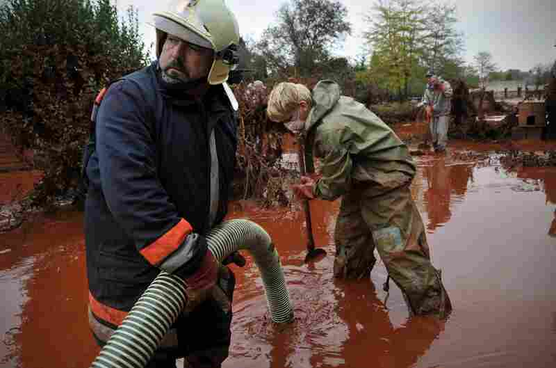 Hungarian firefighters pump sludge from a yard flooded by the toxic mud in Devecser, Oct. 6.
