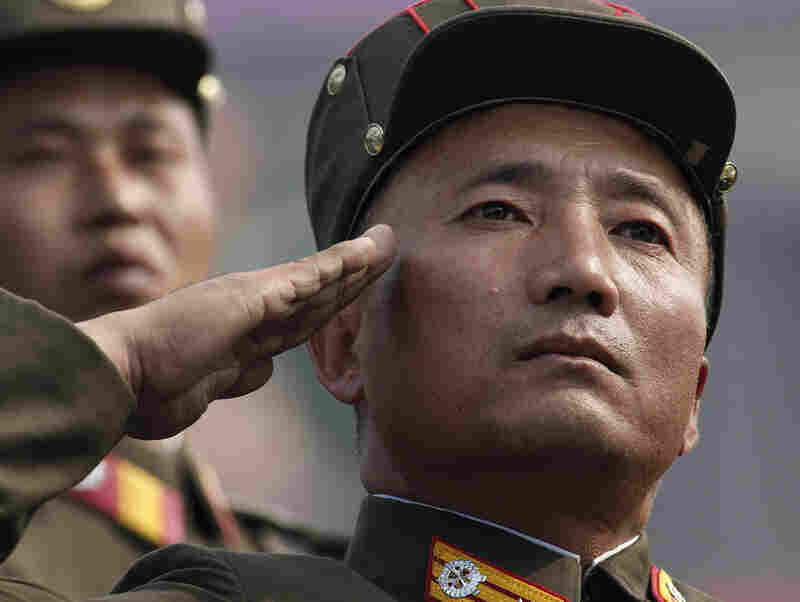 A North Korean soldier salutes as he marches in the massive military parade marking the 65th anniversary of the communist nation's ruling Workers' Party in Pyongyang on Sunday.