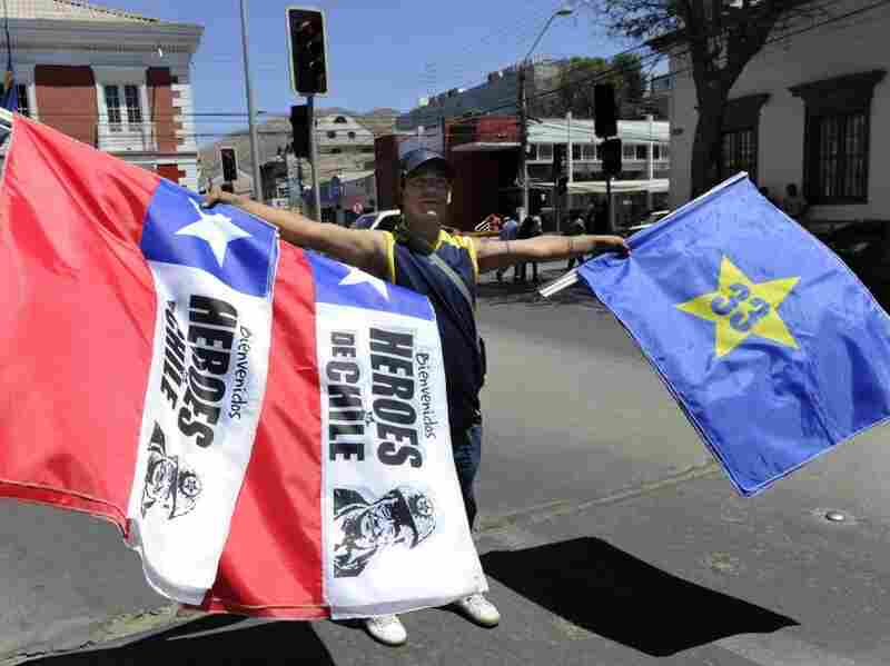 """A peddler sells Chilean and Copiapo flags that say, """"Welcome, Heroes of Chile"""" and """"33"""" in Copiapo."""