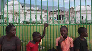 People sit in front of the fence surrounding the crumbling Presidential Palace in Port-au-Prince