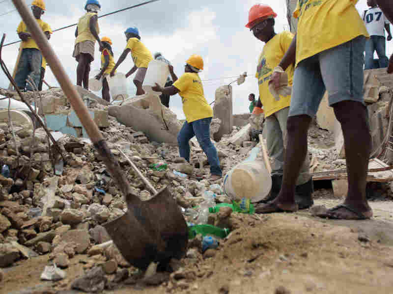 Workers clear rubble from a collapsed building in Port-au-Prince