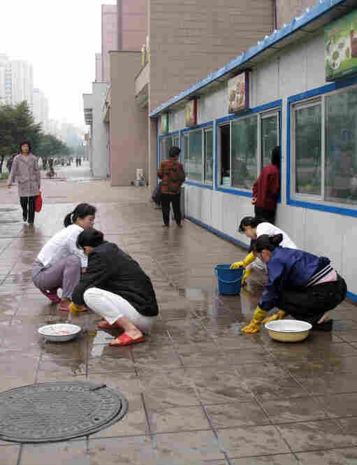 Women scrub the sidewalks of Pyongyang by hand.