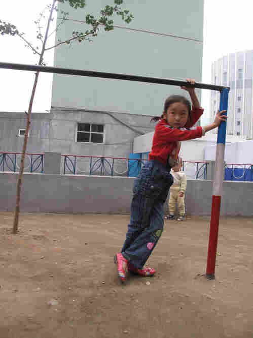 A young girl plays in a dilapidated playground in Pyongyang.