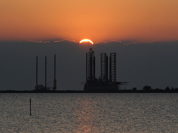 The sun sets over an oil platform waiting to be towed out into the Gulf of Mexico at Port Fourchon in Louisiana.