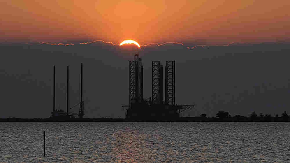 The sun sets over an oil platform