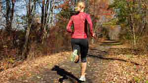A woman runs along a dirt road in the woods.
