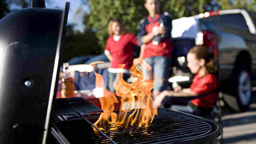 A barbecue grill flares as football tailgaters gather in the background