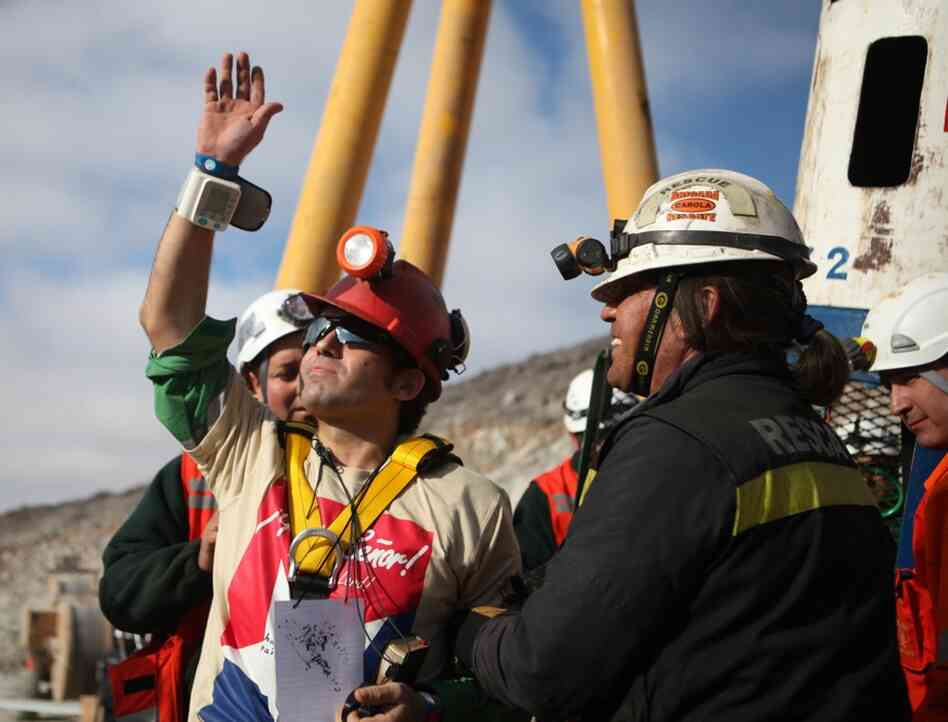 Miner Alex Vega waves upon surfacing from the mine. The men have become national heroes in Chile.