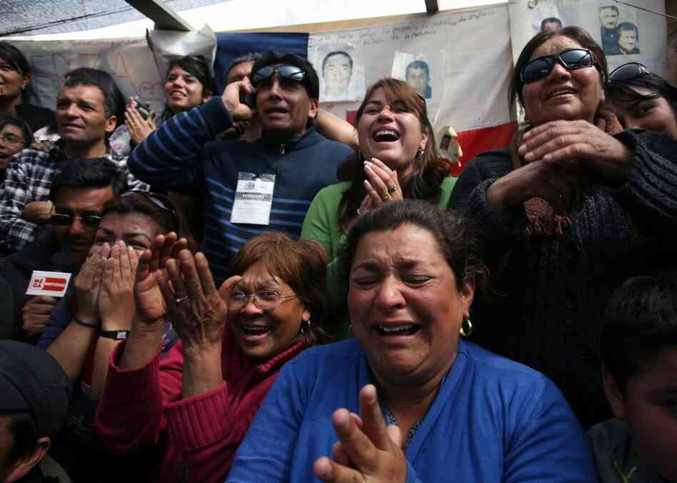 Relatives of miners Victor Zamora and Carlos Barrios cheer after they were pulled out of the mine. The miners ascended to the surface like clockwork at a rate of one or two an hour.