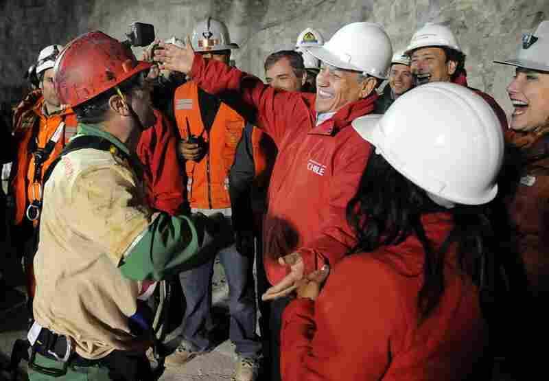 Chilean President Sebastian Pinera hugs the second rescued miner, Mario Sepulveda, after Sepulveda reaches the surface. Pinera has been deeply involved in the rescue, which had become a matter of national pride.
