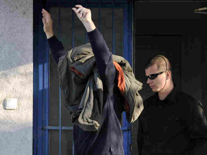 Zoltan Bakonyi is escorted by a police officer after being released from police custody.